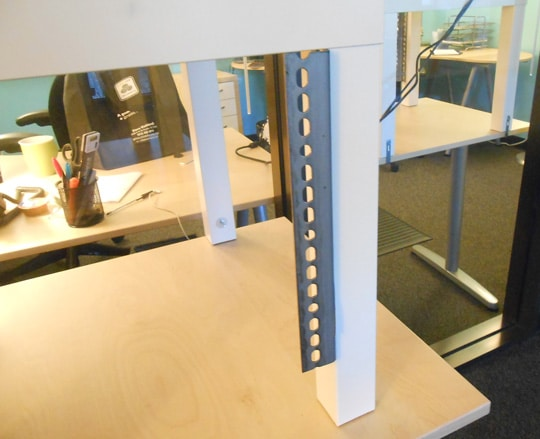Angle bracket mounted to the standing desk